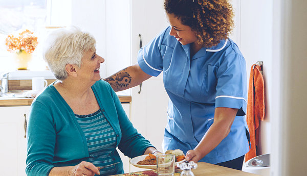 elderly woman and caregiver smiling