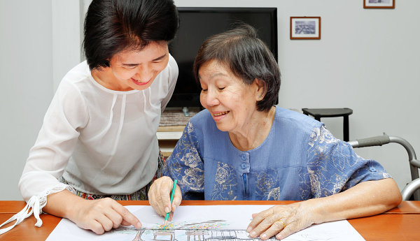 elderly woman and caregiver drawing